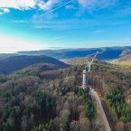 Knapp die Hälfte des ersten Turmes steht. Die Baustelle aus der Luft, mit Ausblick in die Schweiz.